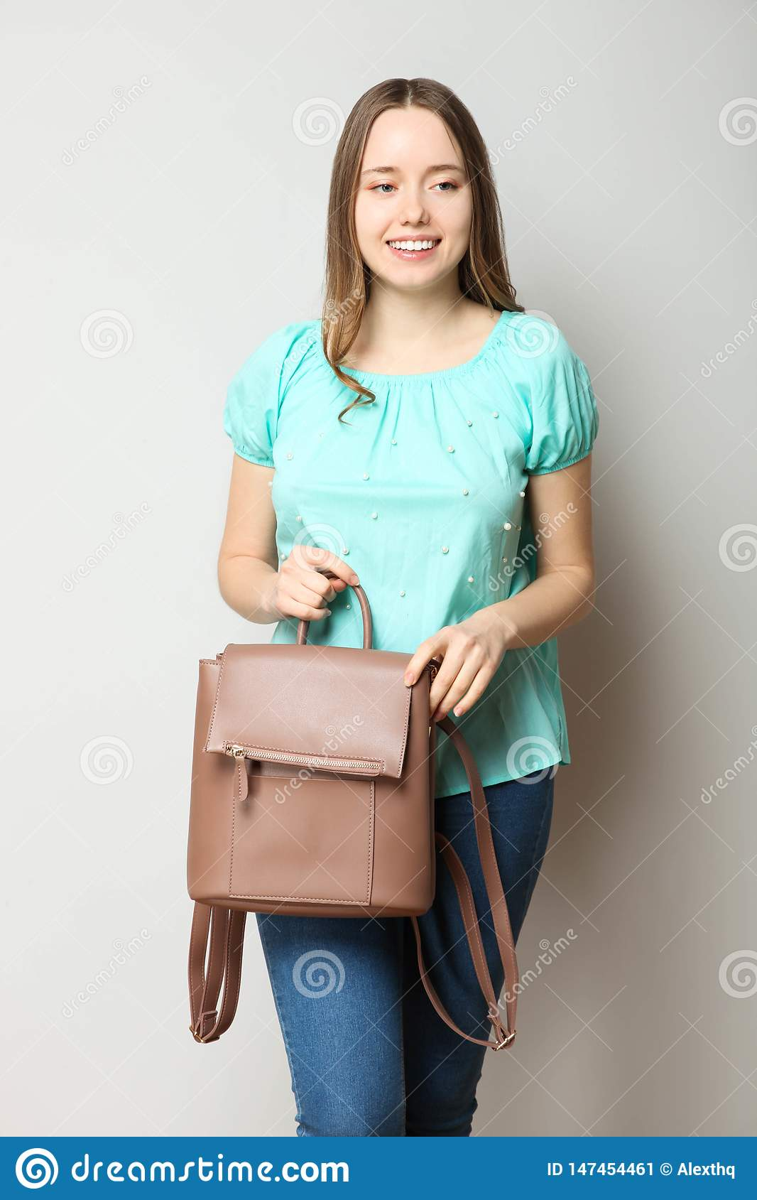 Student in classic casual comfortable clothes with fashionable backpack