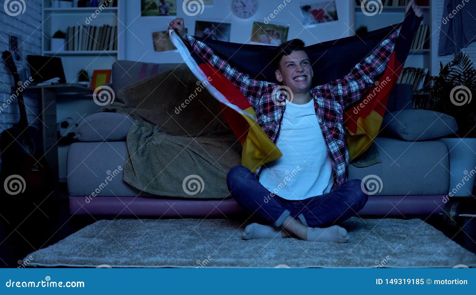 Student, der deutsche Flagge, st?tzendes nationales Fu?ballteam, Sport h?lt