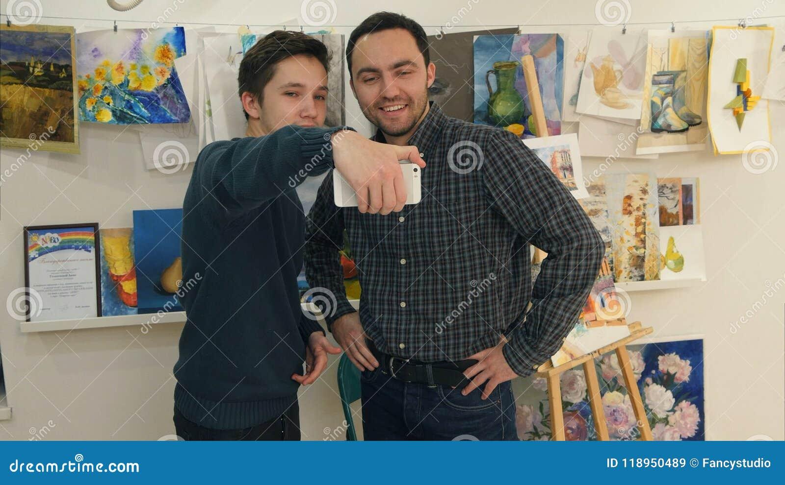 Student, der Hände mit seinem Kunstlehrer rüttelt und selfie am Telefon nimmt