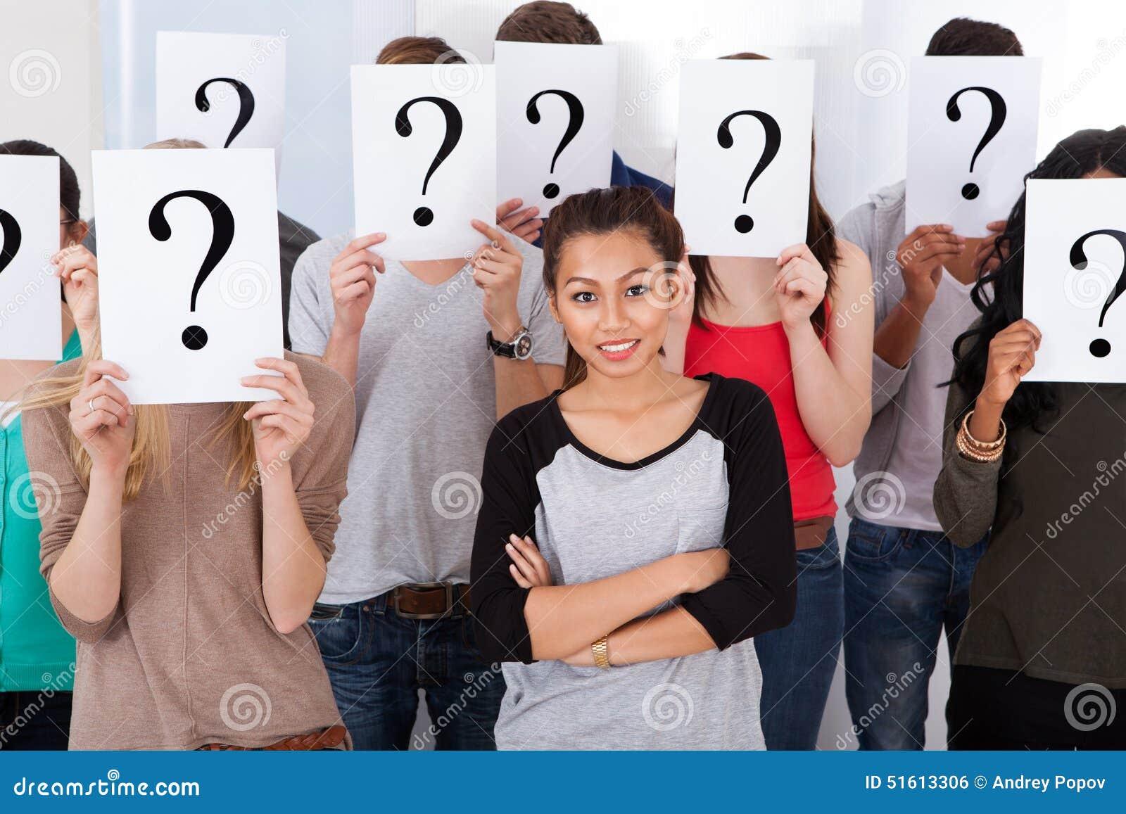 Student die door klasgenoten wordt omringd die vraagtekentekens houden