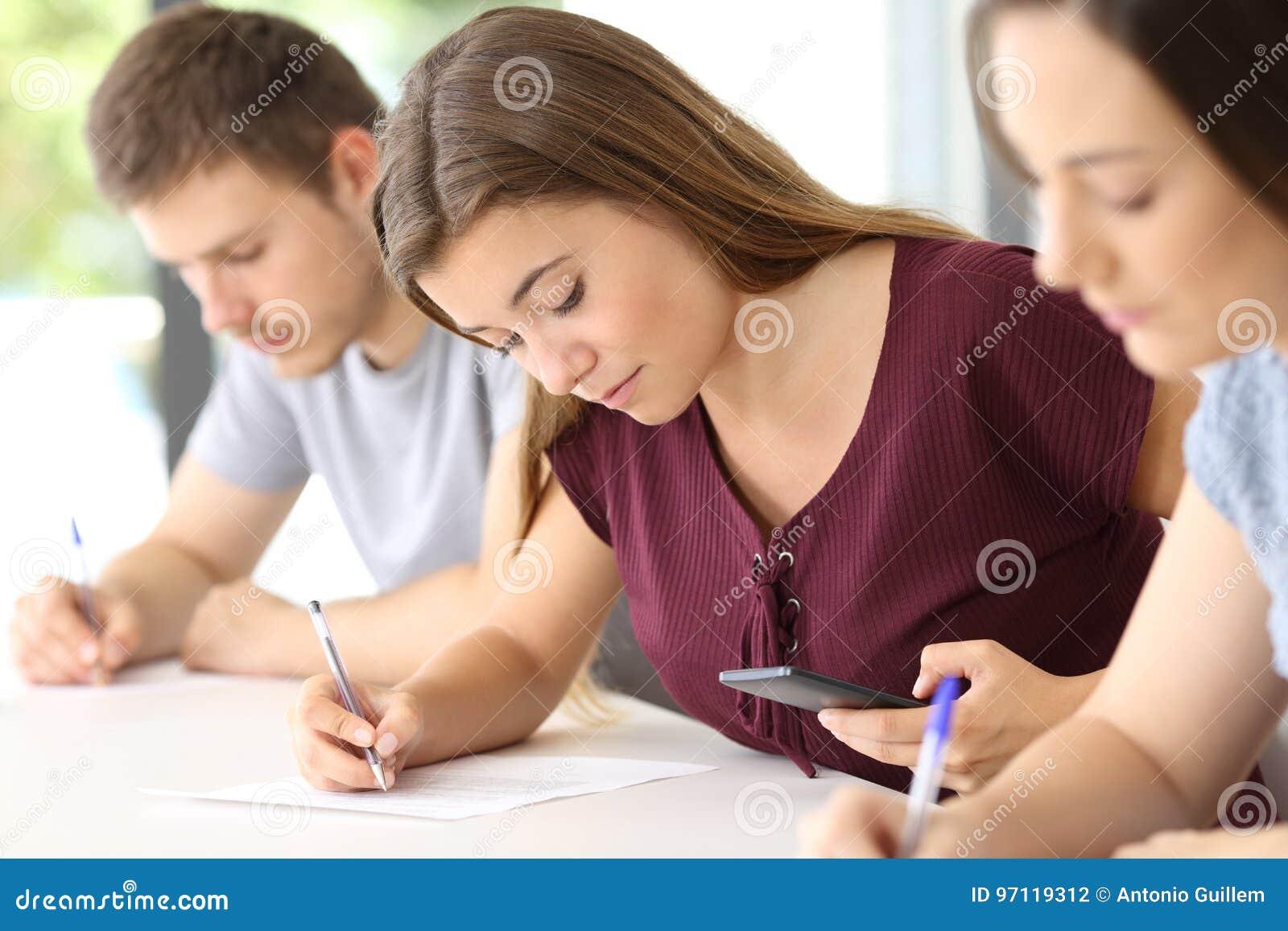 Student die een slimme telefoon met behulp van tijdens een examen