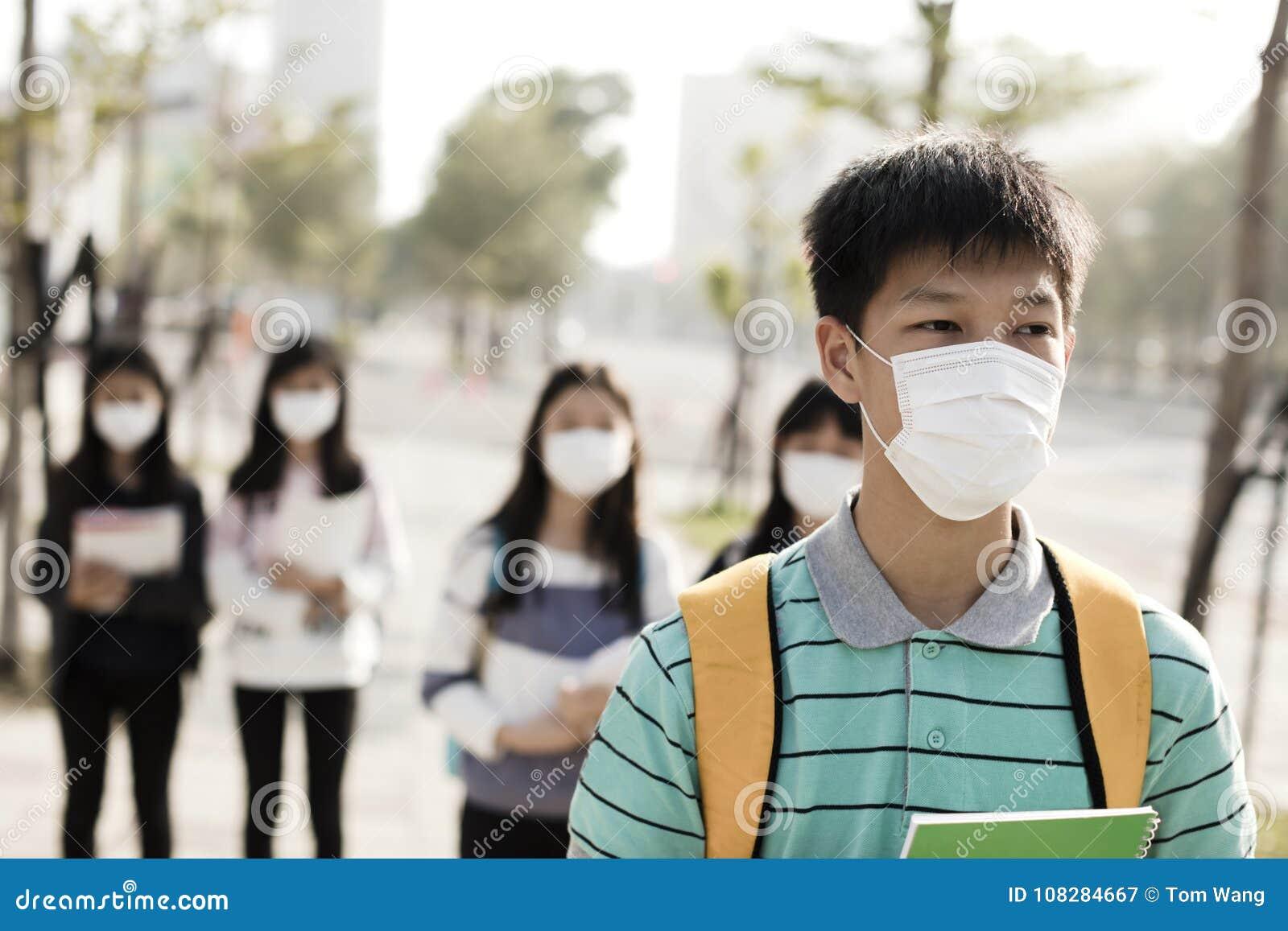 Student die mondmasker dragen tegen smog in stad
