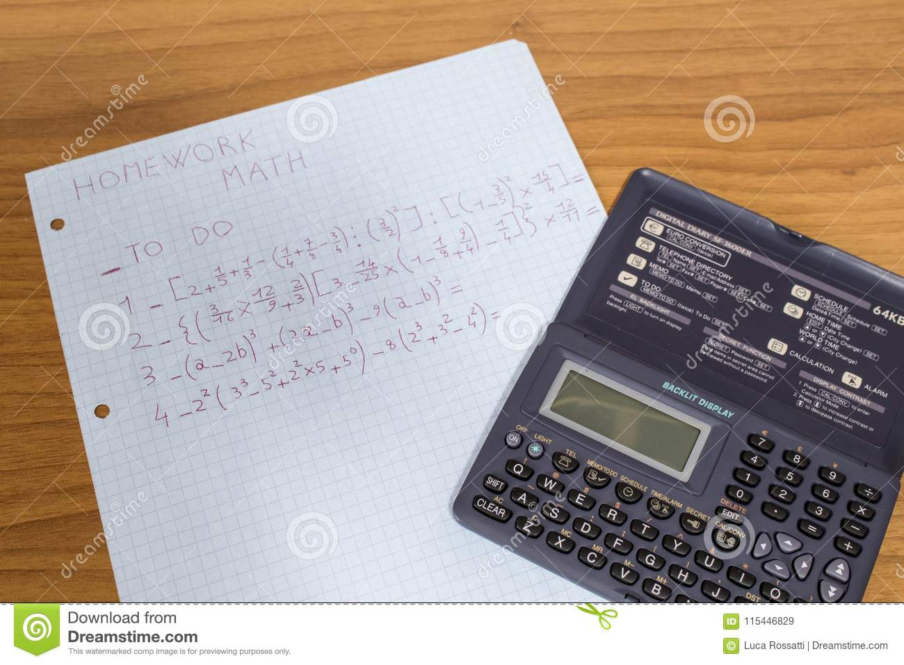A Student Is Doing Math Homework With A Calculator On A Wood