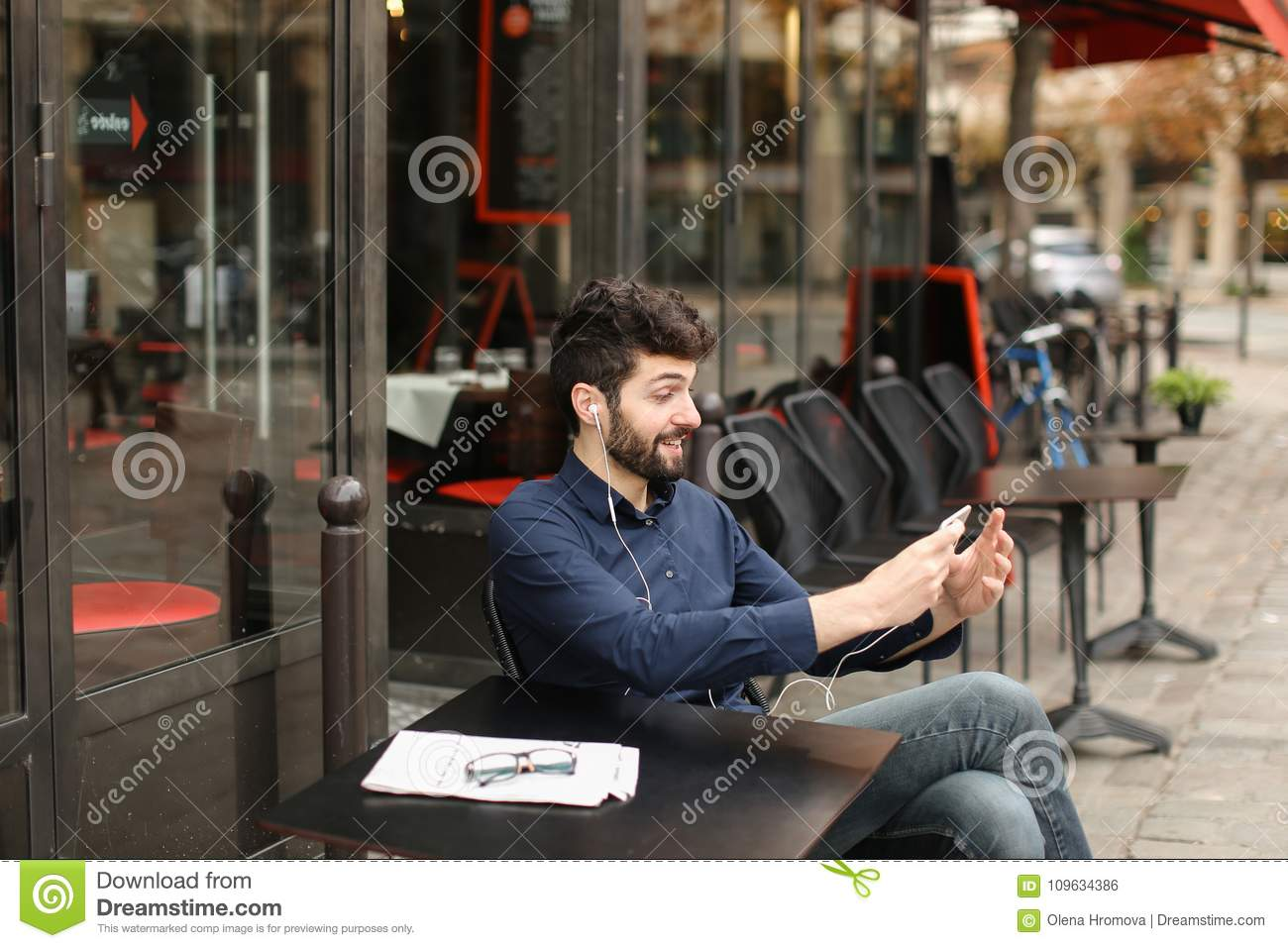 Student Listening To Music With Smartphone And Earphones At