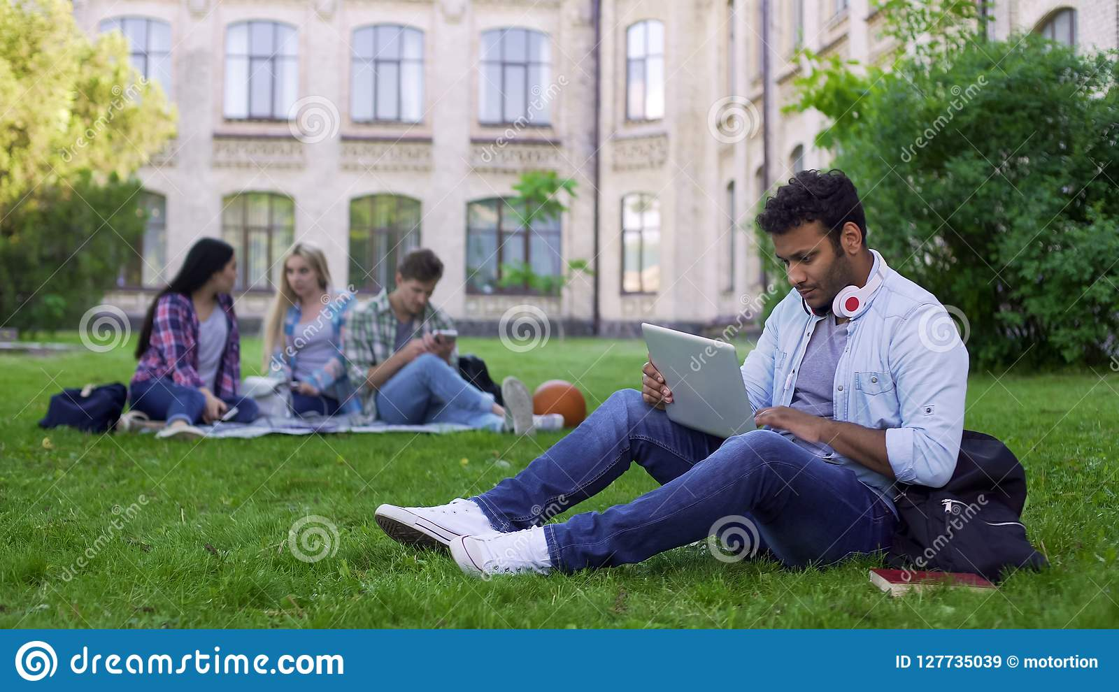 Student för blandat lopp som använder bärbara datorn som direktanslutet sitter på gräs på universitetsområde, utbildning