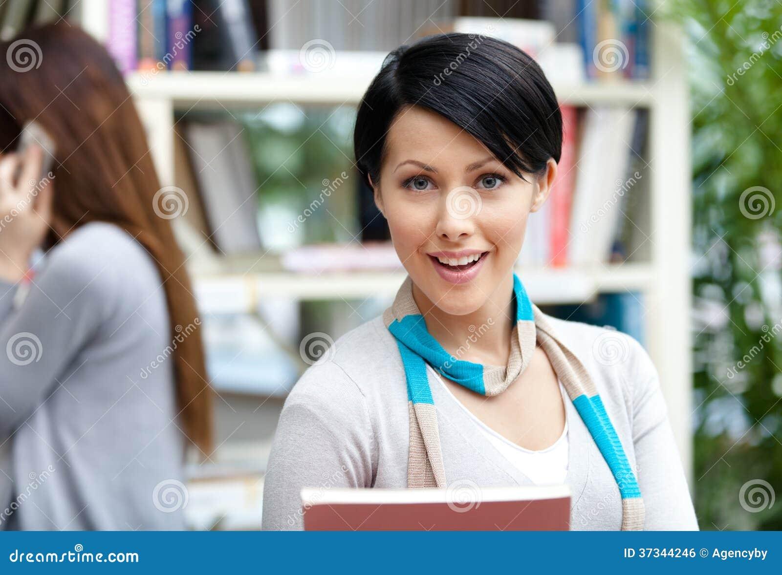 Student för ung kvinna på arkivet mot bokhyllor