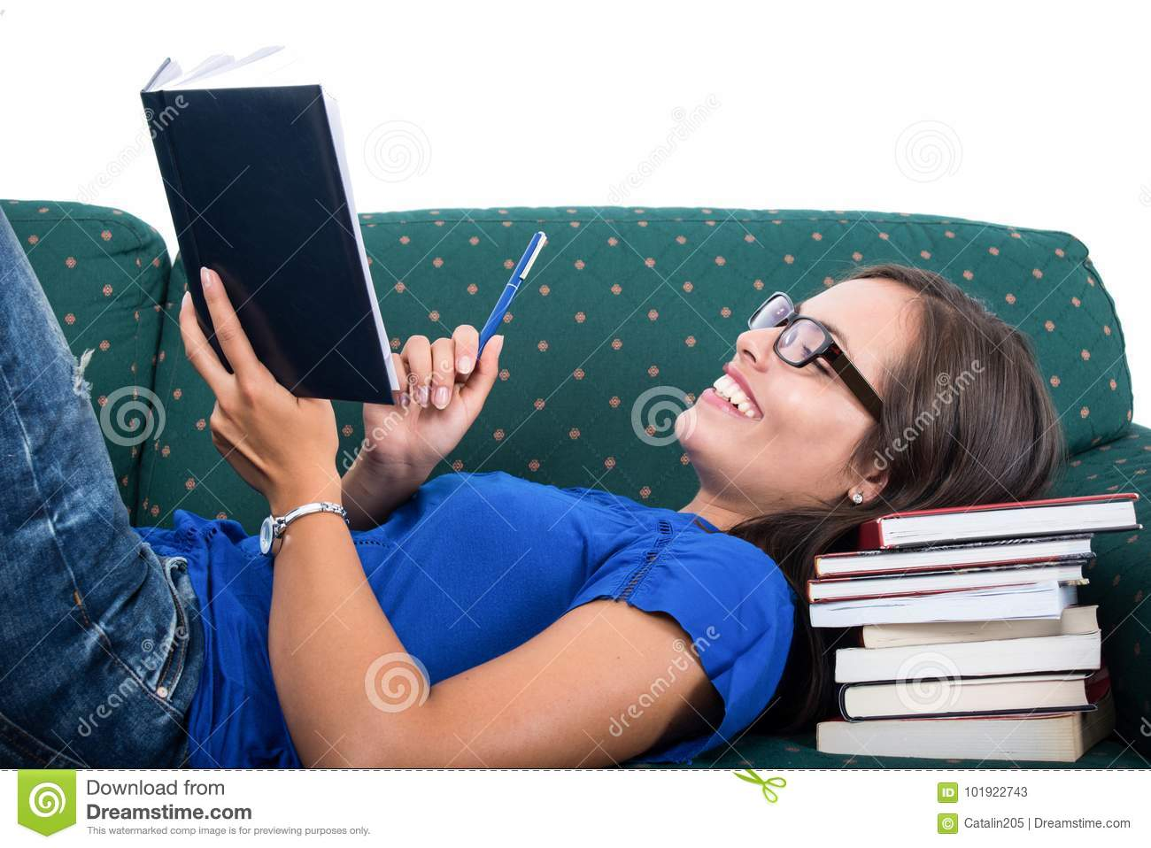 Student girl laid on couch smiling holding notebook