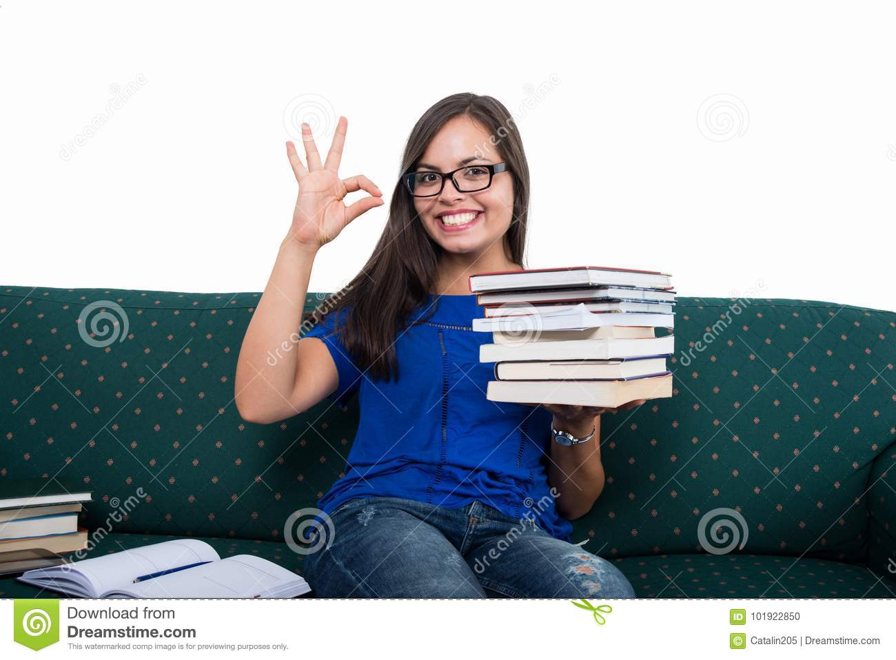 Student girl sitting on couch showing ok holding books