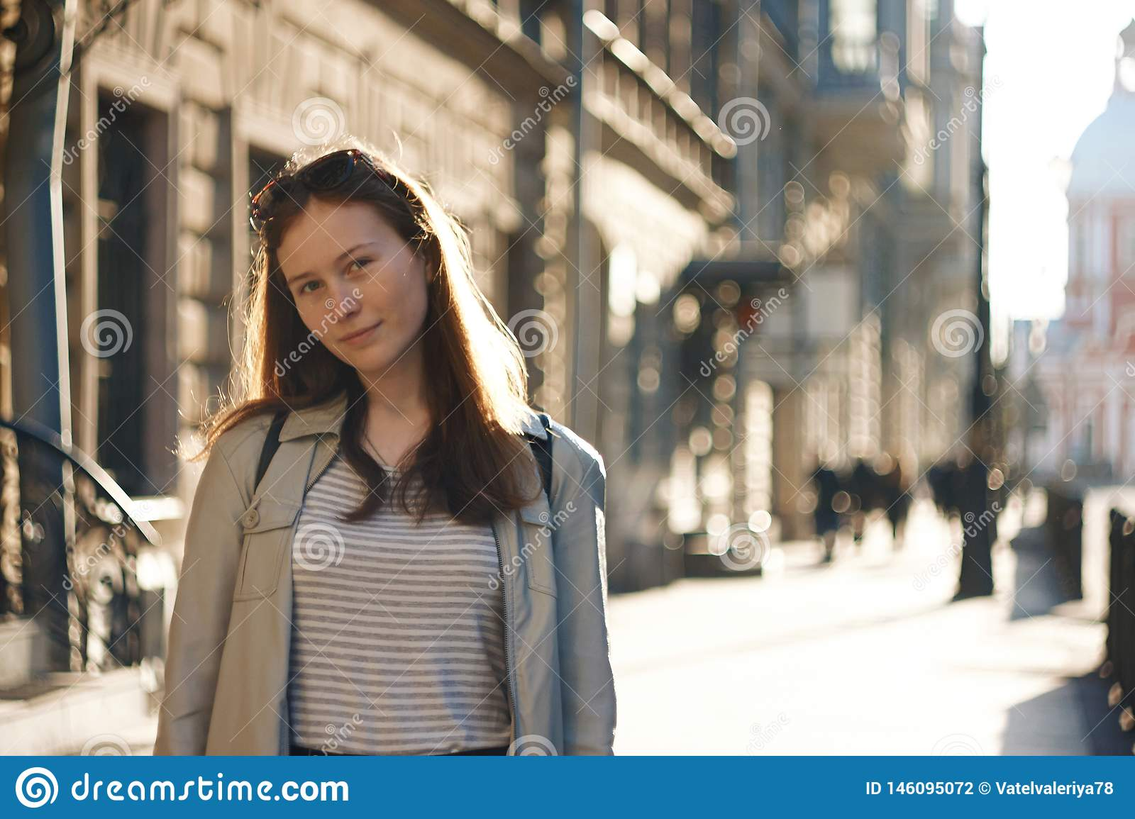 A student girl stands on the background of a city street