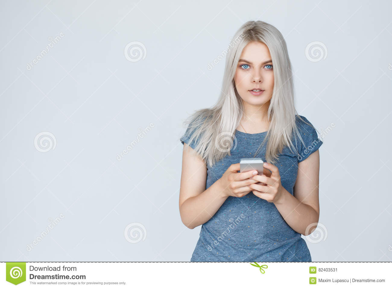 2e6431aa760b Young woman with blond hair typing on mobile phone, over grey background.  Student girl in t-shirt with copy space
