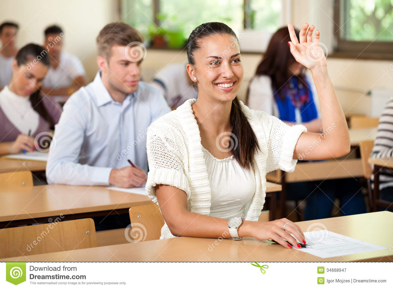 student giving answer in class with his hand raised stock image