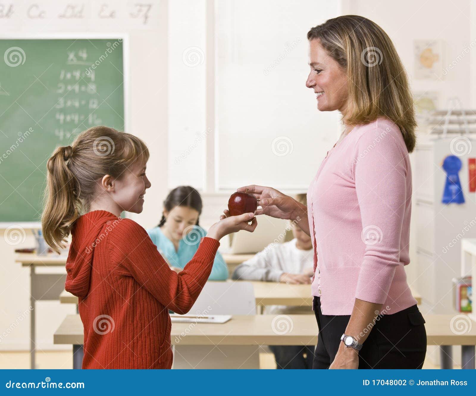 student giving teacher apple stock photography