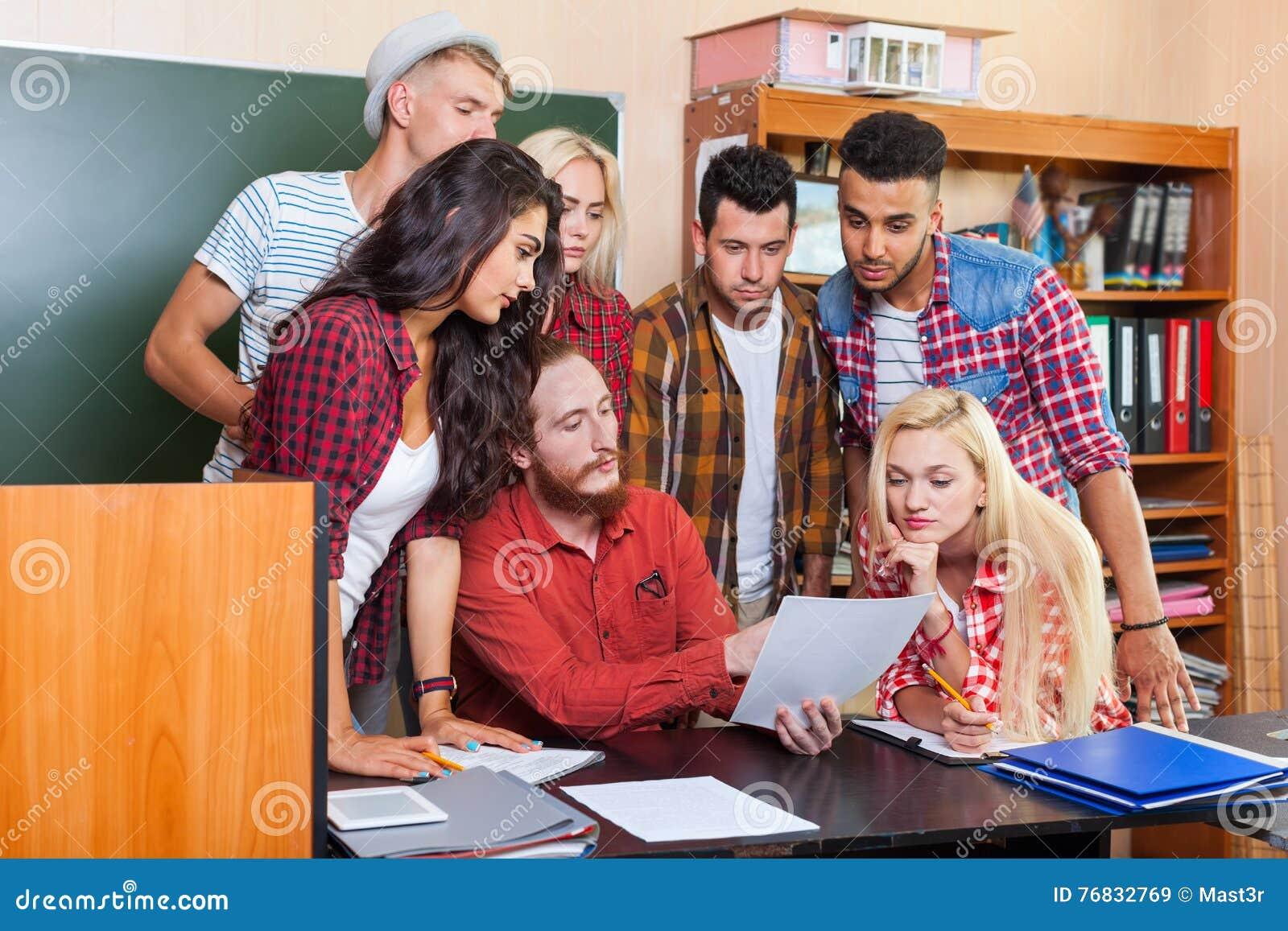 Student High School Group die Document Document met Professor Sitting At Desk, Jongerenleraar Discuss bekijken
