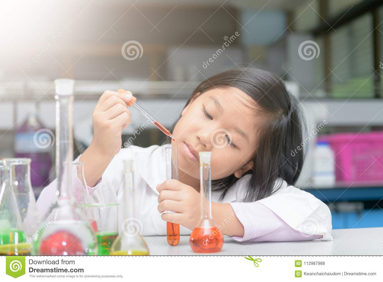 Student in lab coat making experiment with test tube