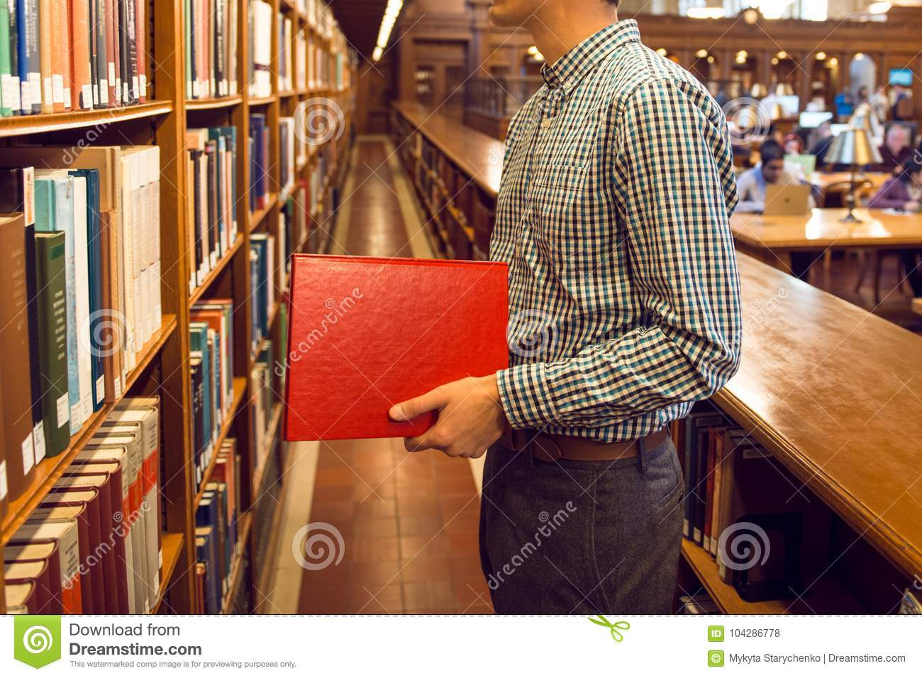 Student Man Taking The Book From Bookshelf In Public Library And Going To Read Download Preview