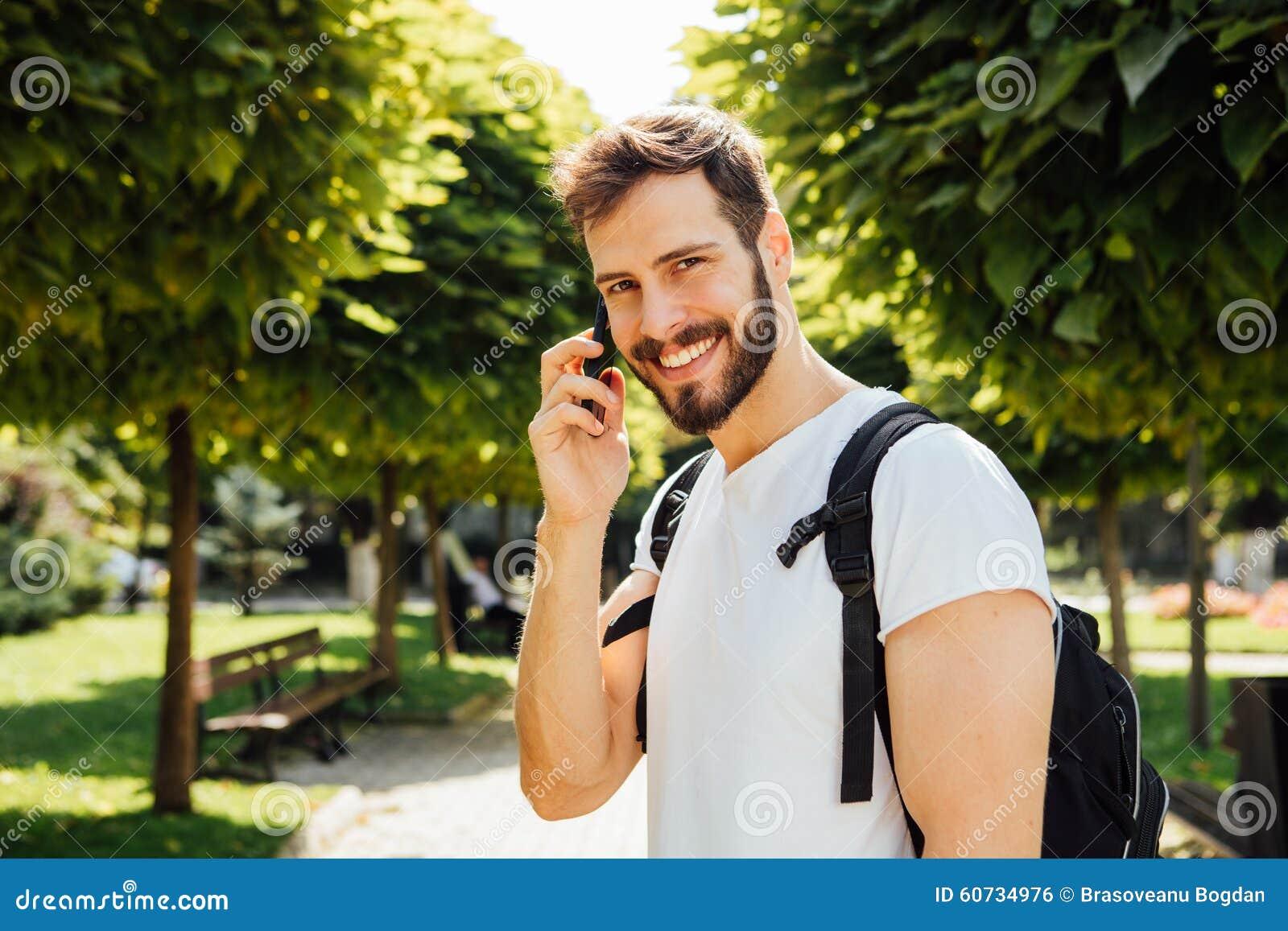 Student met rugzak die bij cellphone spreekt