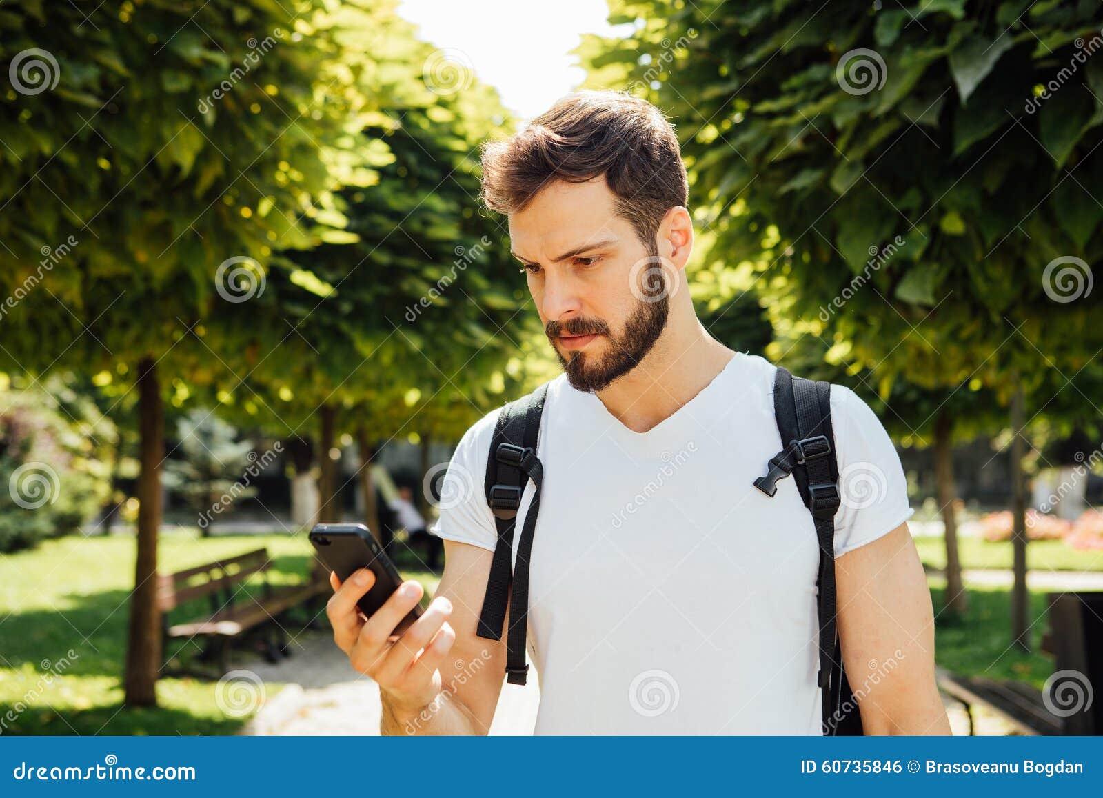 Student mit Rucksack sprechend am Mobiltelefon