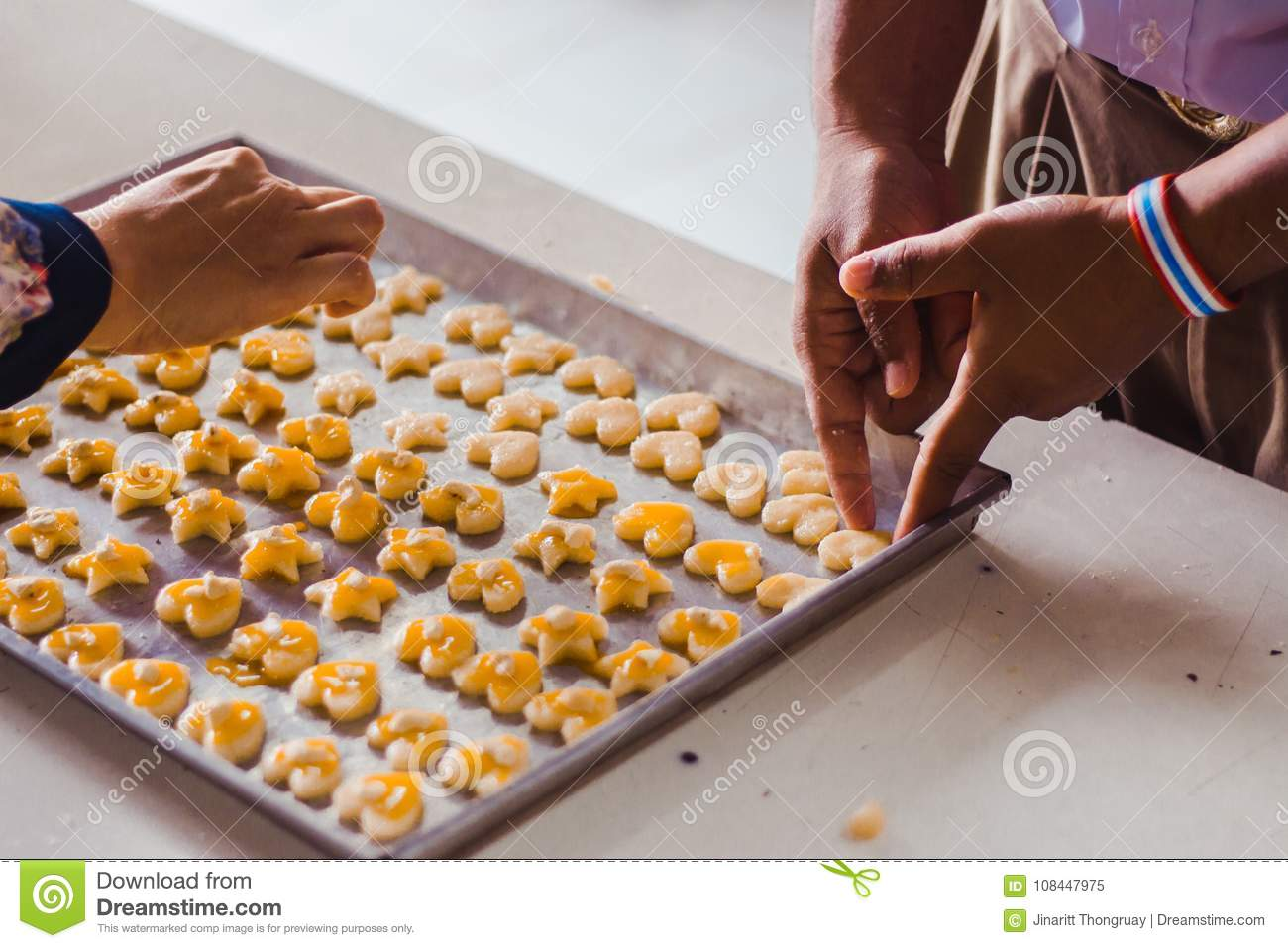 Student `s hands make Singapore cookies from dough in school.