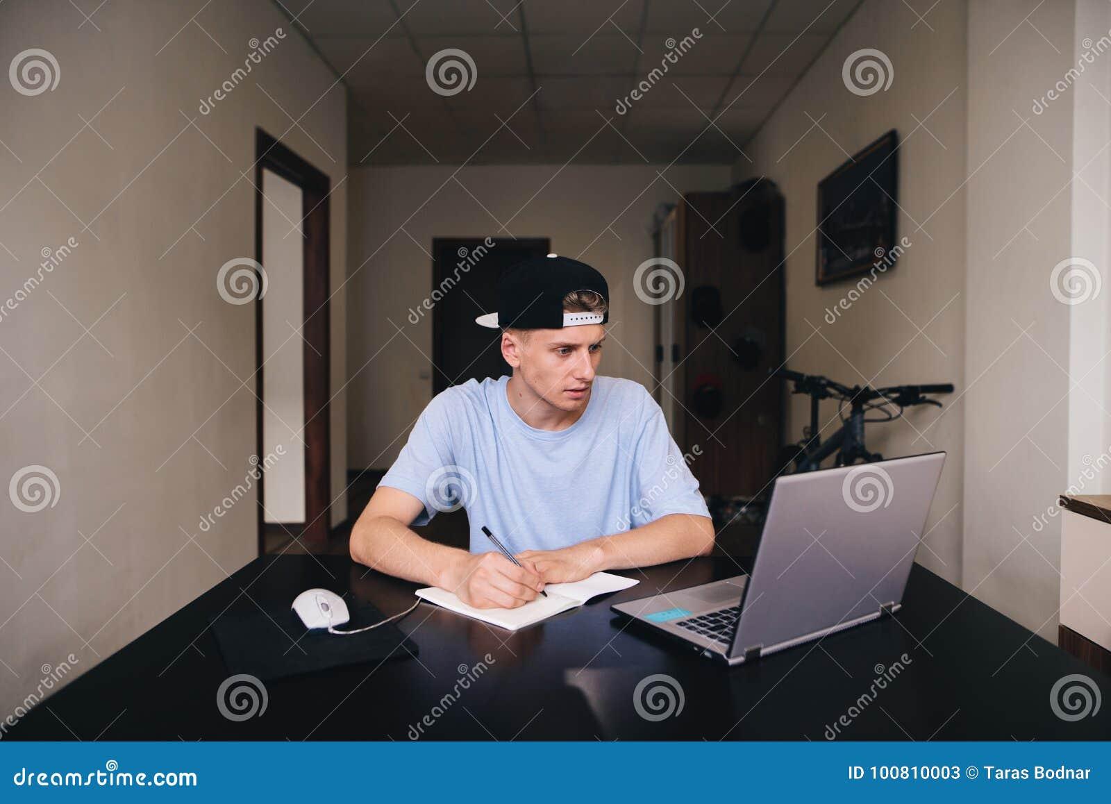 Student studiert zu Hause Der Jugendliche betrachtet den Computer und schreibt den Text zum Notizbuch