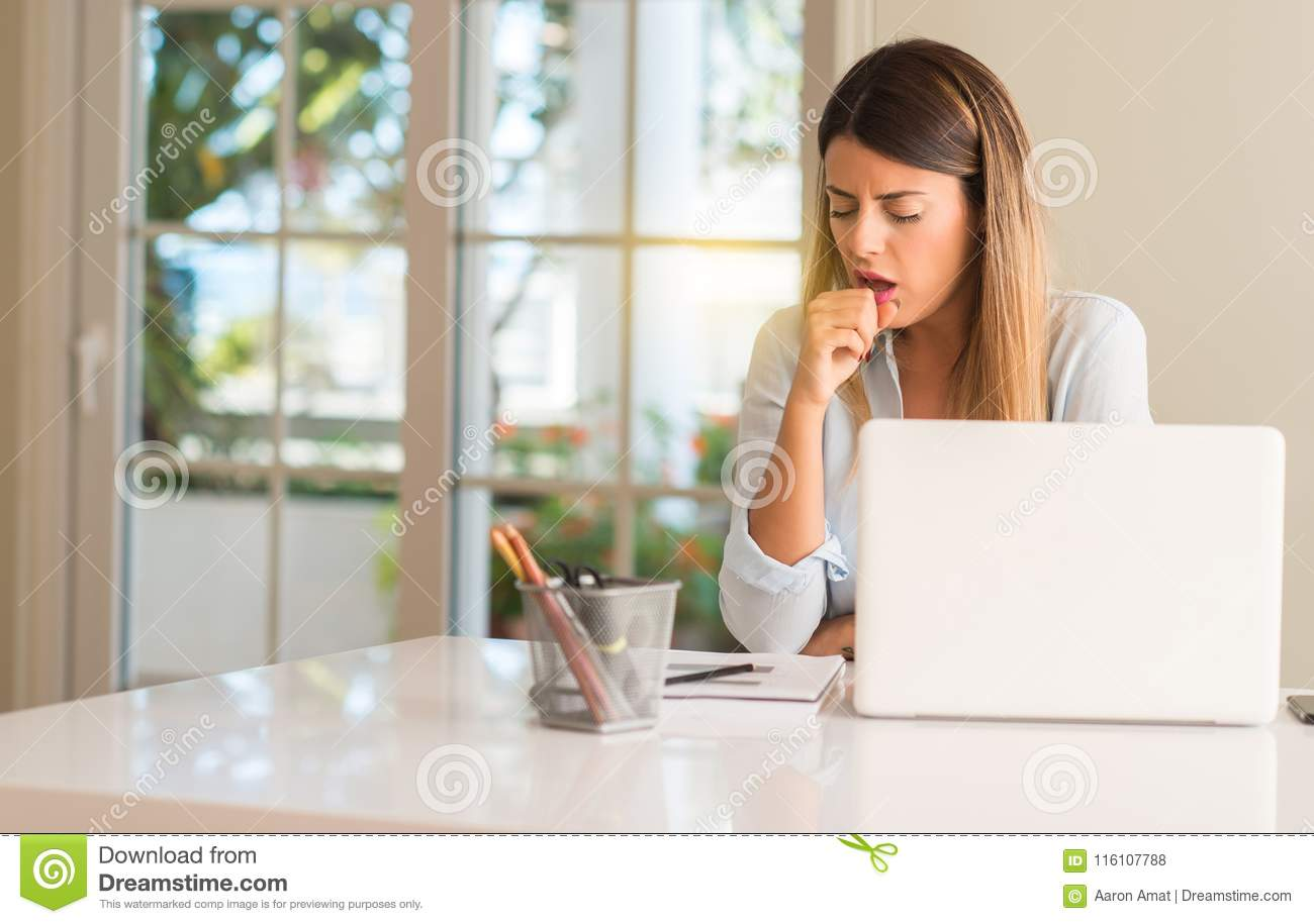 Young beautiful student woman with laptop at table, at home