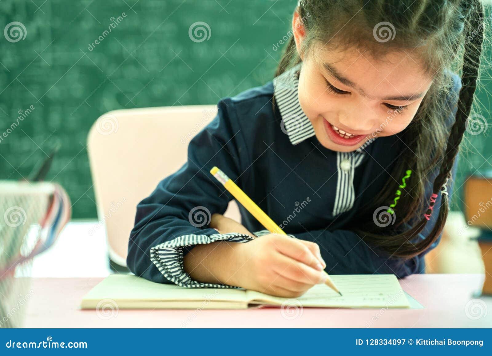 Studente asiatico della scuola primaria che studia compito in aula