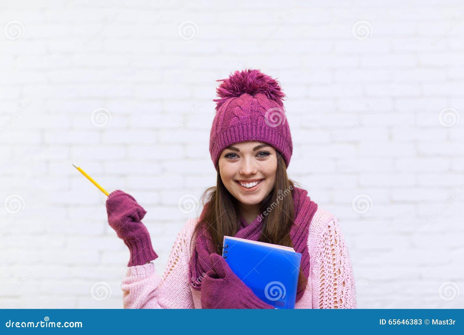 Studente attraente Girl Hand Gesture per copiare sorriso dello spazio in matita rosa della cartella della tenuta del cappello