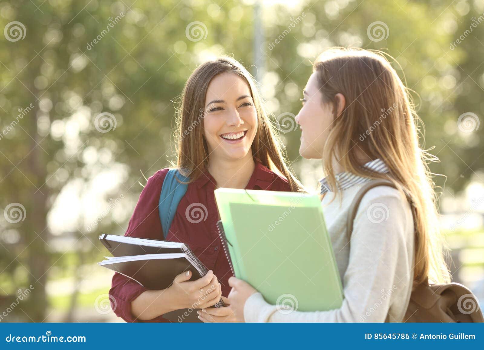 Studenten, die in einem Campus gehen und sprechen