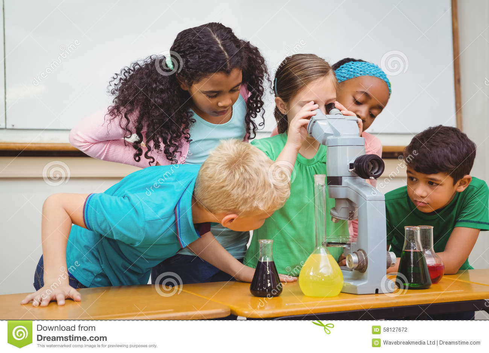 Nette schüler der suche durch mikroskop an der grundschule