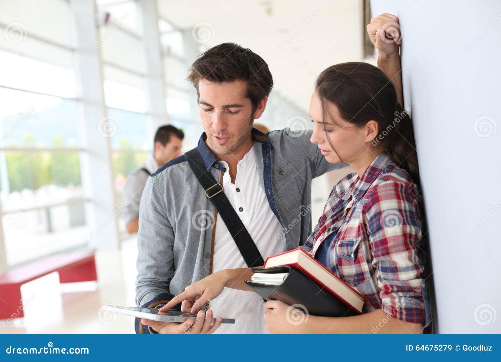 Studenten die zich in gang bevinden die tablet gebruiken