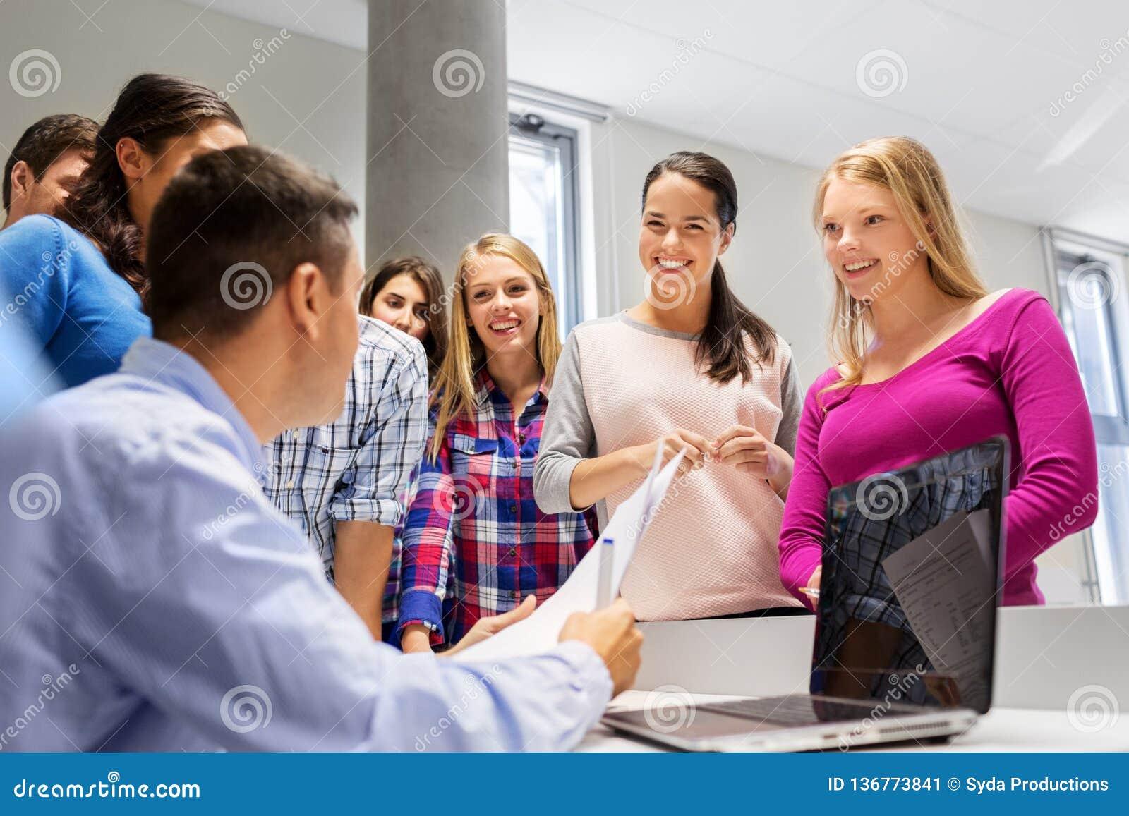 Studenten en leraar met documenten en laptop
