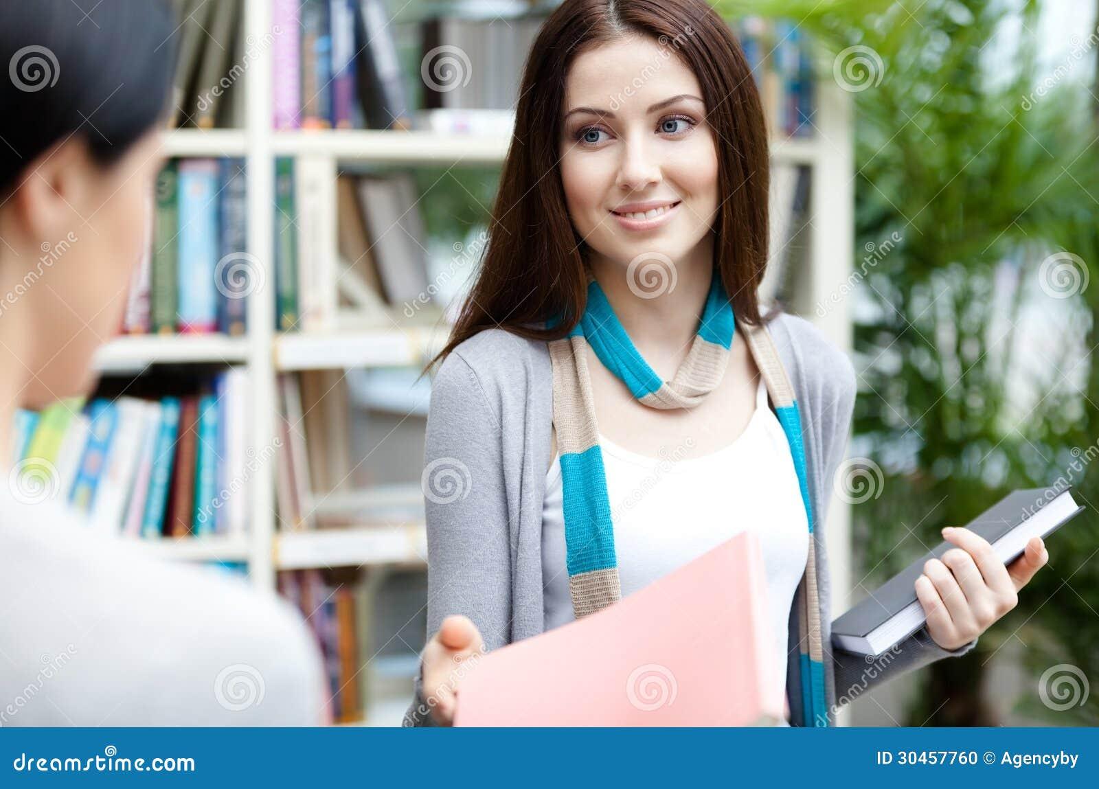 Studenten erbjuder en bok till hennes vän