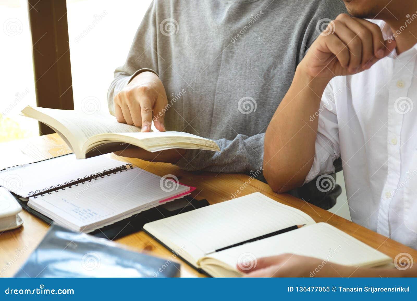 Studenten hilft dem Freund, der abhängiges zusätzliches in der Bibliothek unterrichtet und lernt getrennte alte Bücher