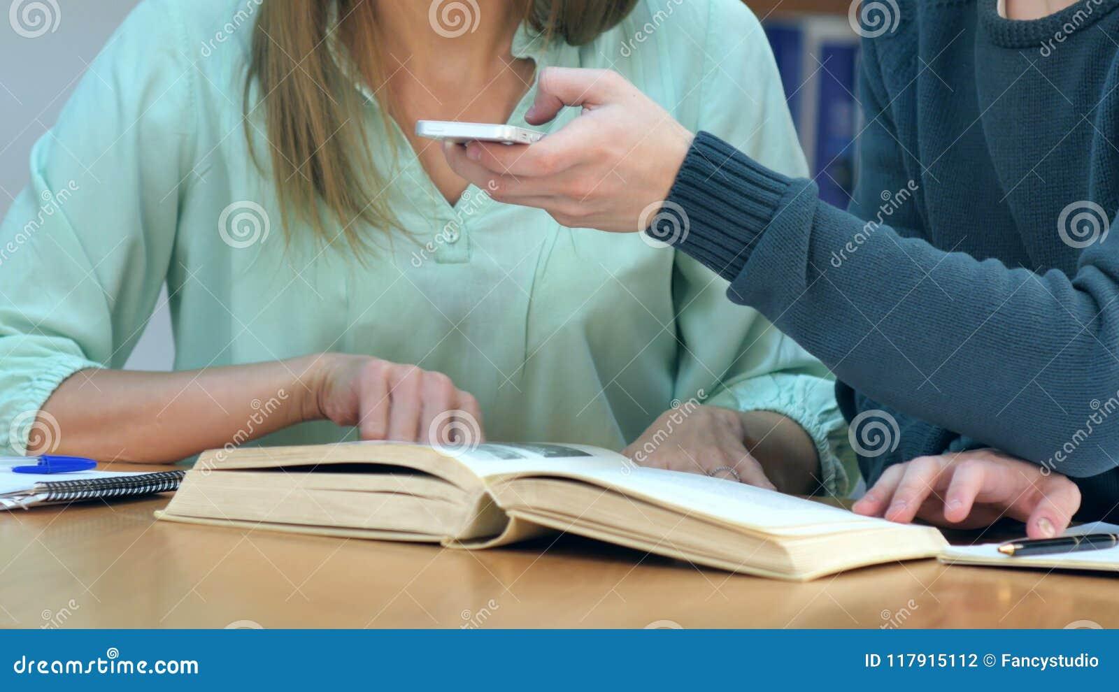 Studenten met smartphones die beeld van boekenpagina nemen en spiekpapiertje in schoolbibliotheek maken