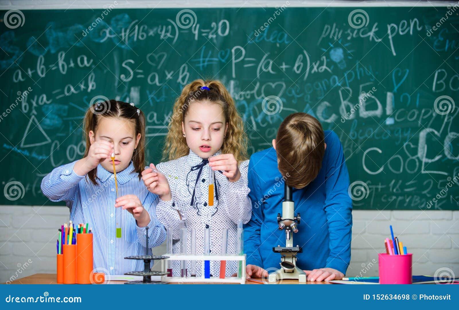 Studentenbiologieexperimente mit Mikroskop im Labor Kleine leere Flaschen Kleinkinder, die Chemie im Schullabor lernen