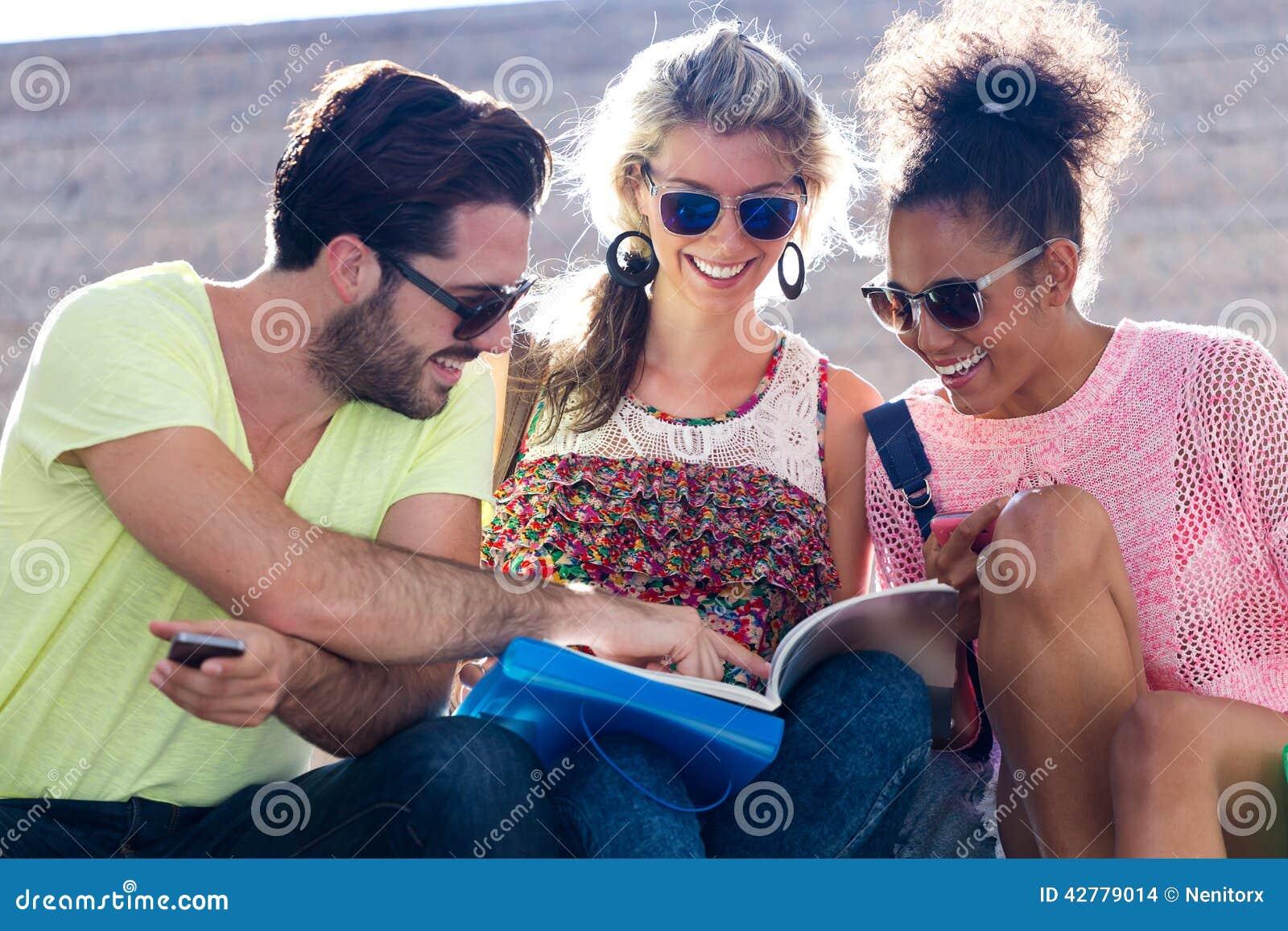Studentengroep die een boek in de straat bekijken