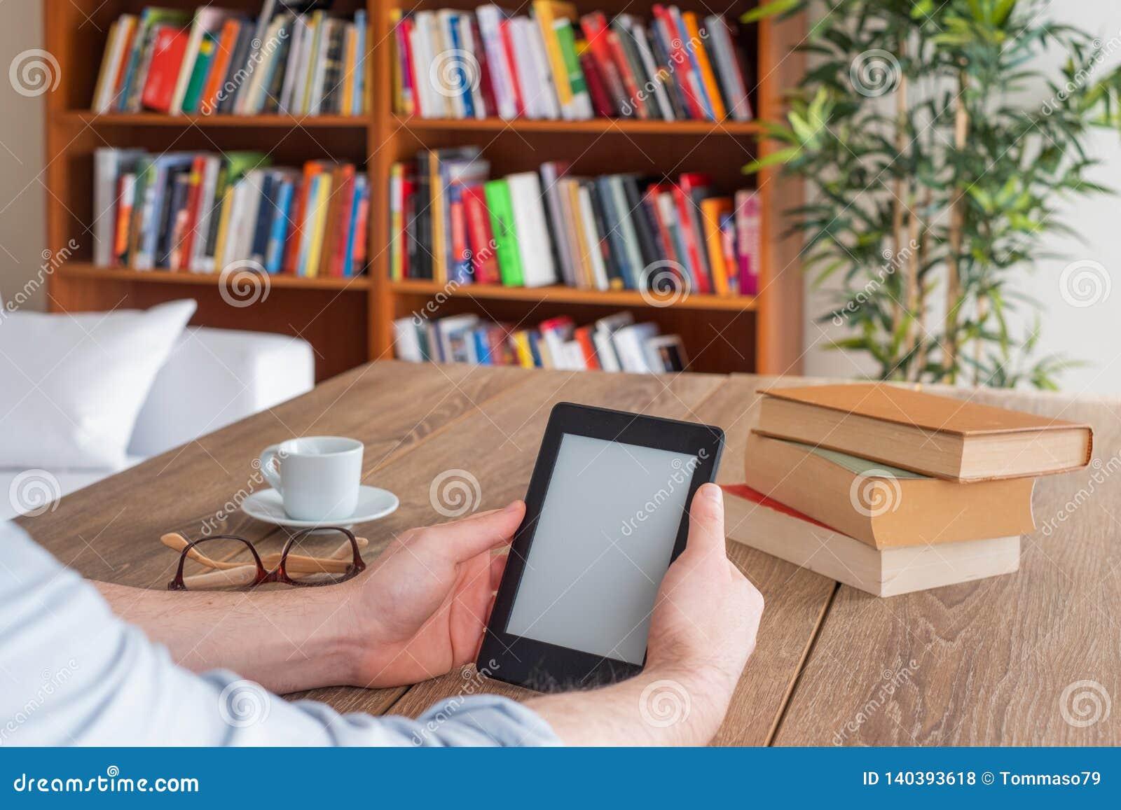 Studentenhände, die zu Hause einen ebook Leser halten