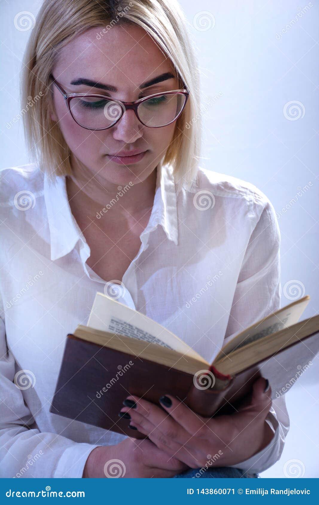 Studentenmädchen, das altes Buch mit Gläsern liest