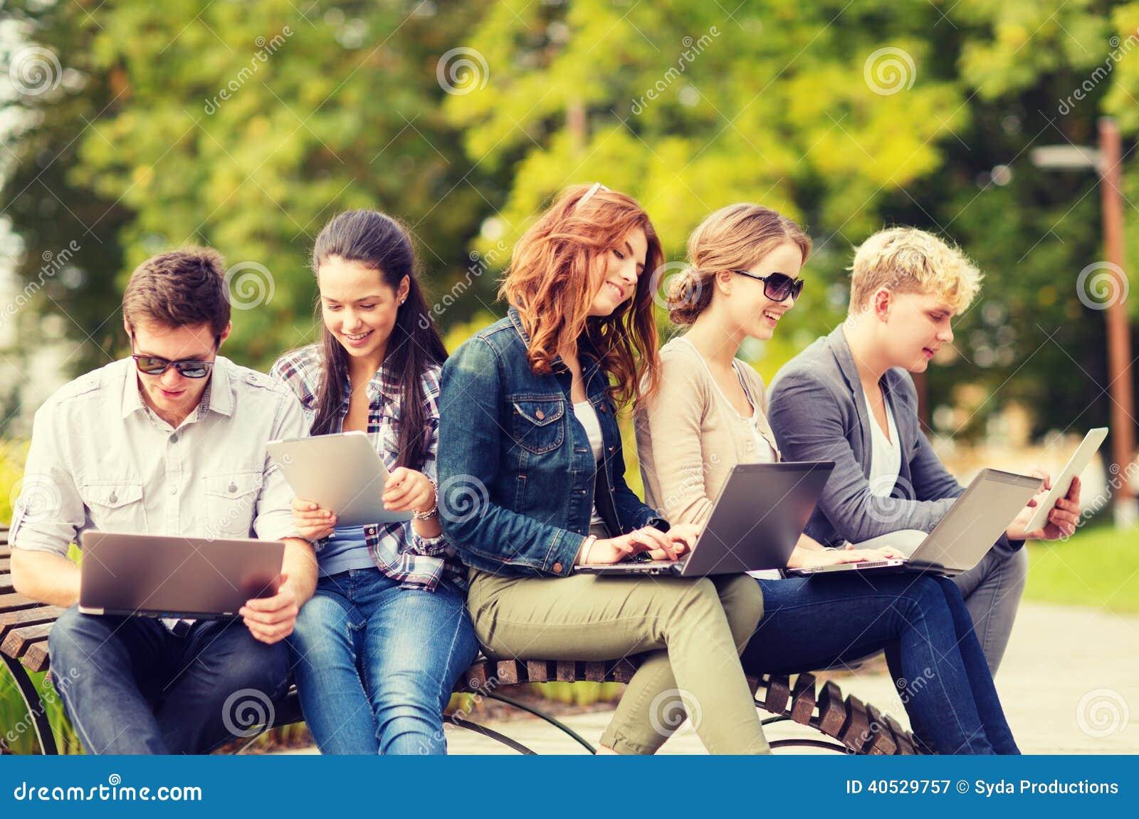 Studenter eller tonåringar med bärbar datordatorer