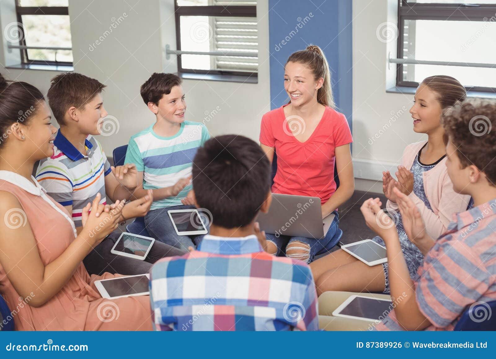 Studenter som uppskattar klasskompisen efter presentation i klassrum