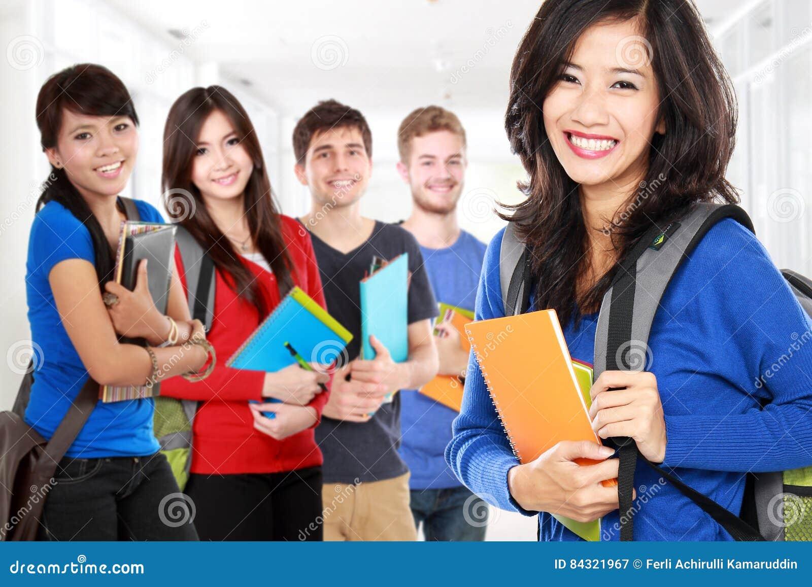 Studentessa ed amici che sorridono alla macchina fotografica
