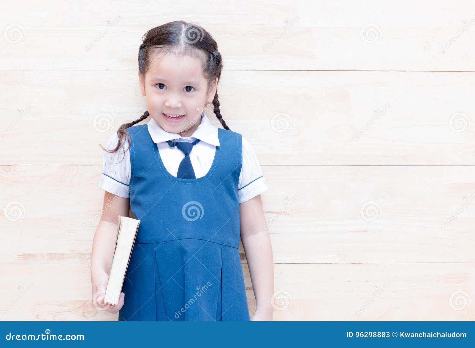 Studentessa sveglia felice in uniforme con il libro