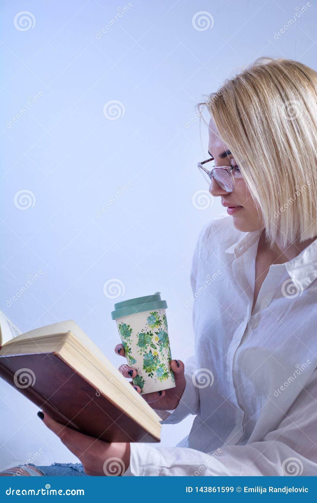Studentflickaläsebok och dricka varmt te från den retro koppen