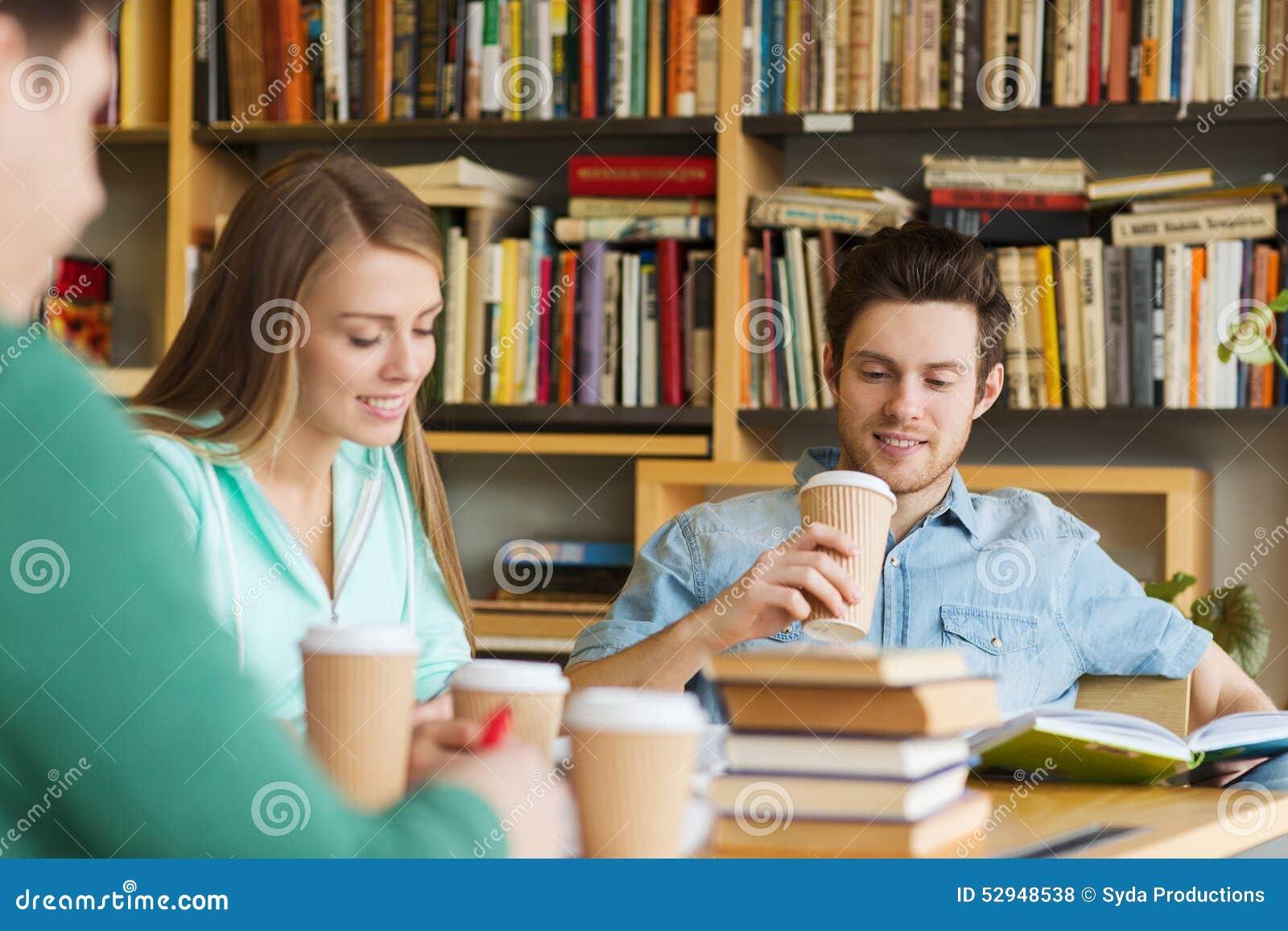 Studenti che leggono e che bevono caffè in biblioteca