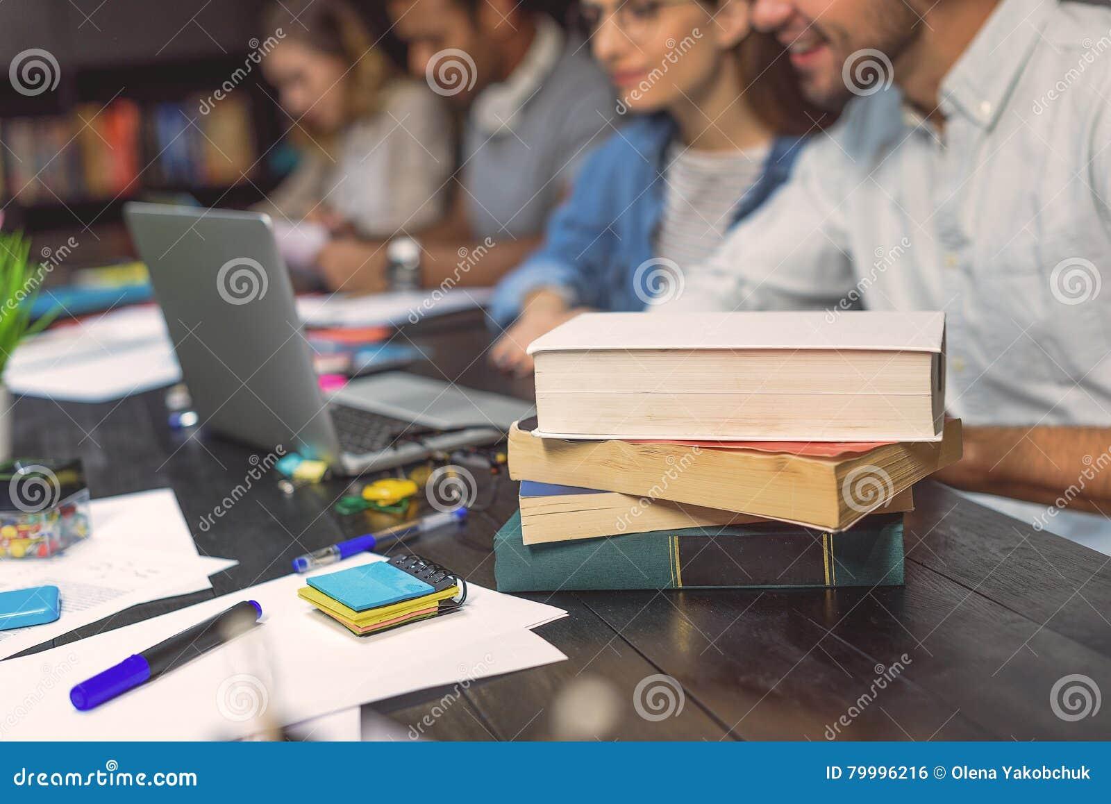 Studenti di college che si siedono insieme e che studiano
