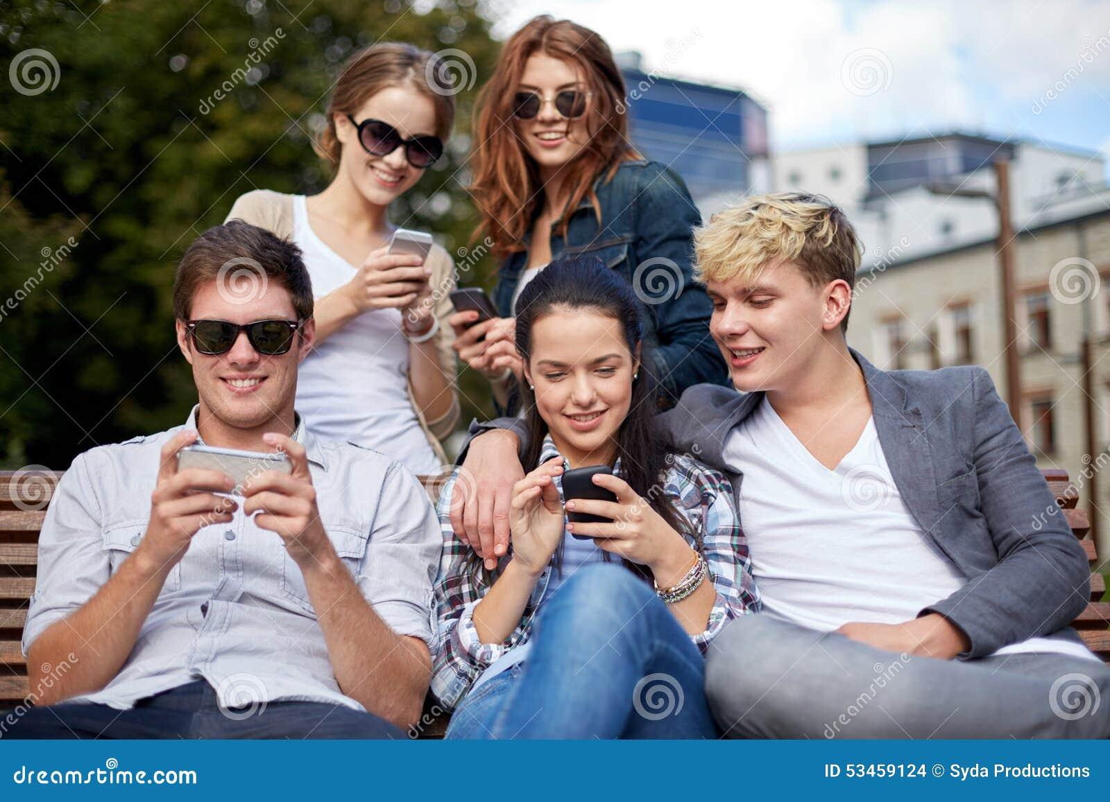 Studenti o adolescenti con gli smartphones alla città universitaria