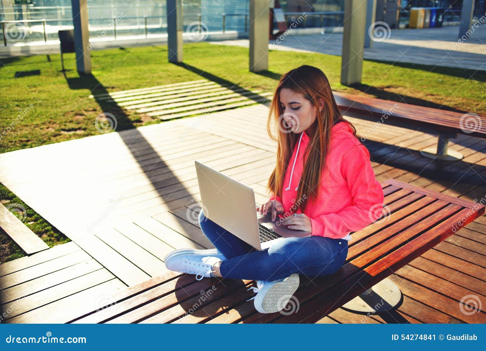 Studentin des blonden Haares, die auf der Laptoptastatur sitzt am Campus schreibt