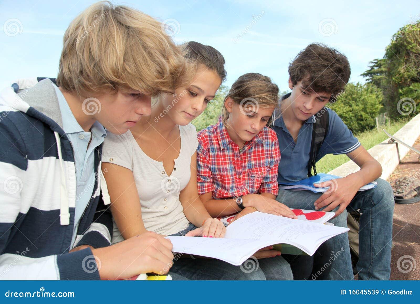 Students with handbooks in school yard