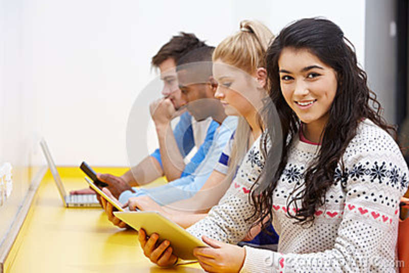 Students Studying In Classroom With Digital Devices