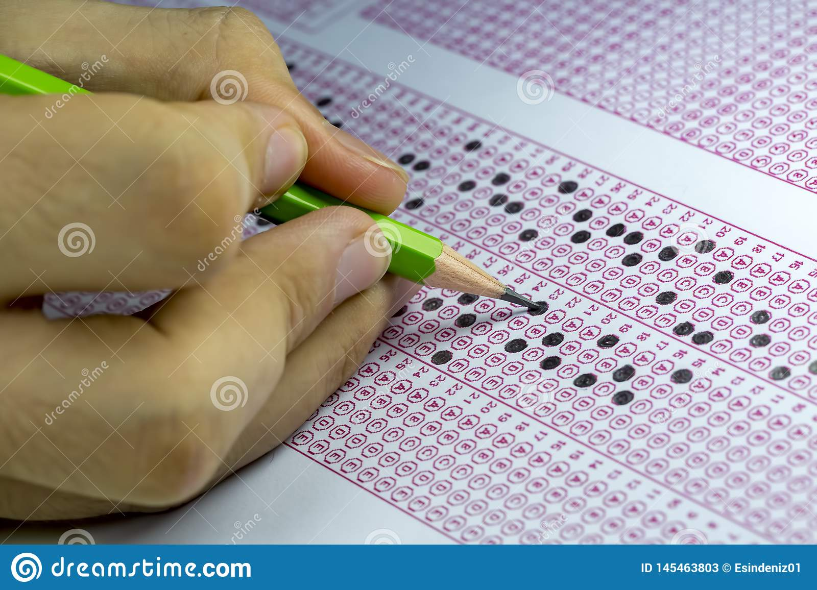 Students taking exams, writing examination room with holding pencil on optical form of standardized test with answers paper