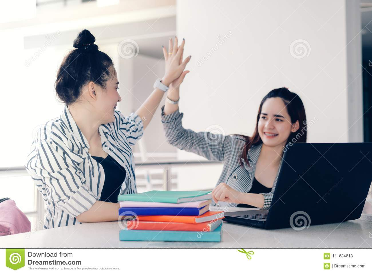 Students women teamwork high five together working study online or homework success project with laptop computer and meeting in un